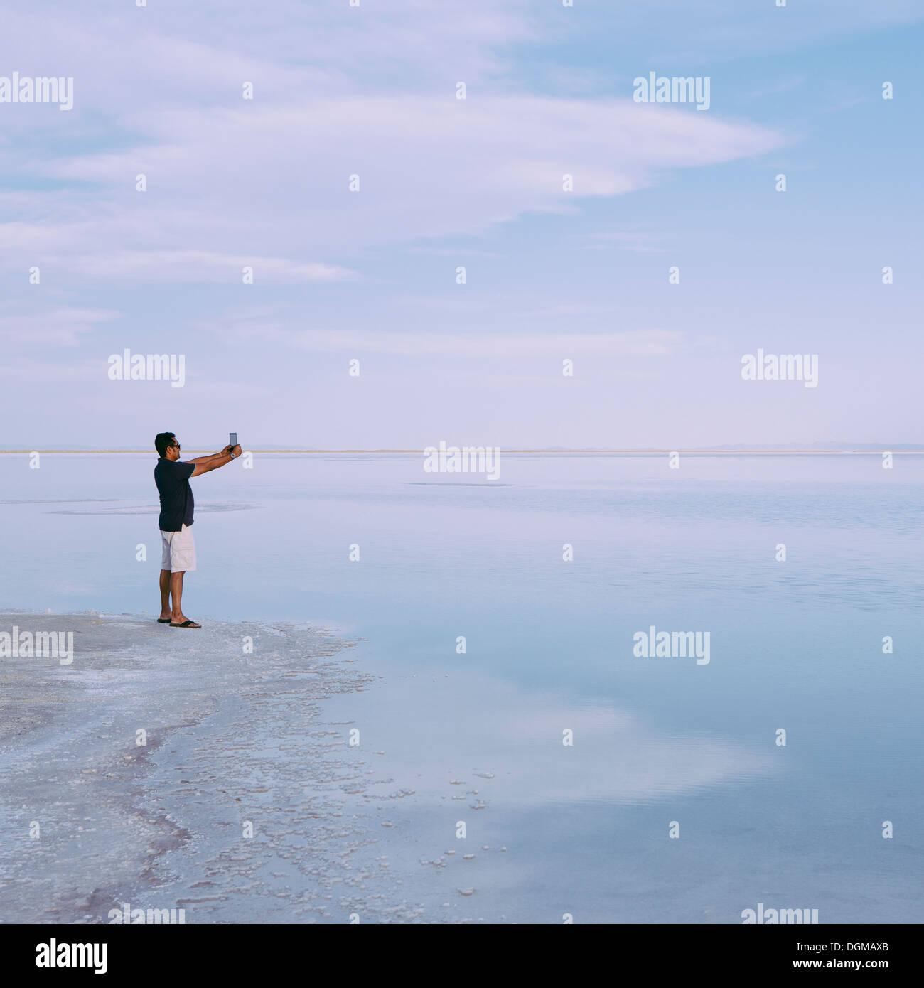 Un uomo in piedi sul bordo dell'allagato Bonneville Saline al tramonto, scattare una fotografia con un dispositivo tablet, vicino Wendover. Immagini Stock