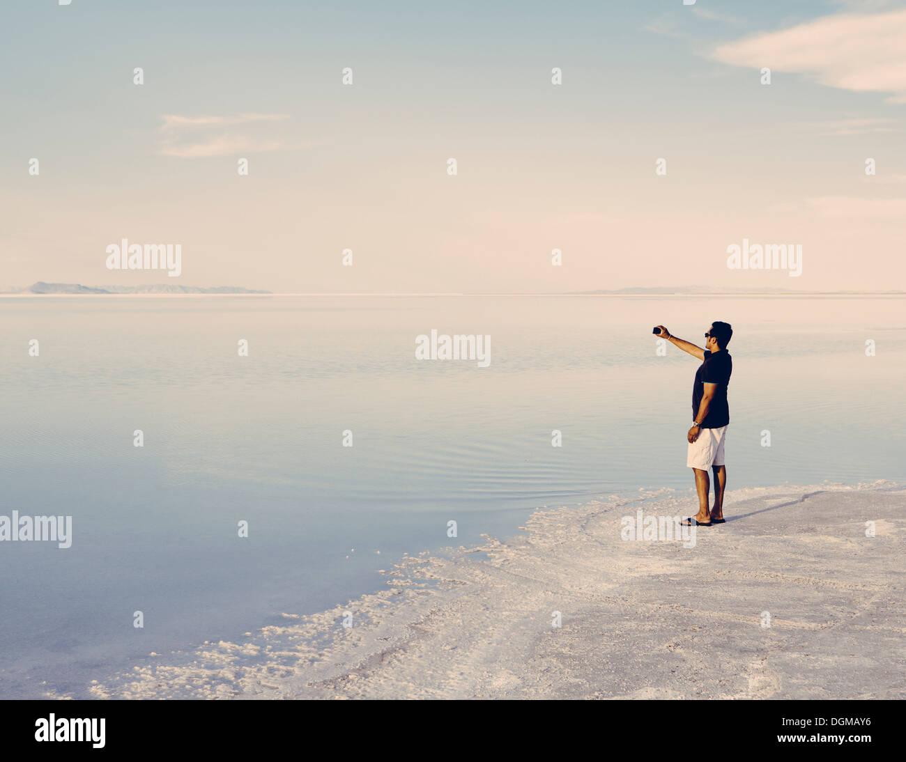 Un uomo in piedi sul bordo dell'allagato Bonneville Saline al tramonto, scattare una fotografia con un telefono intelligente Immagini Stock