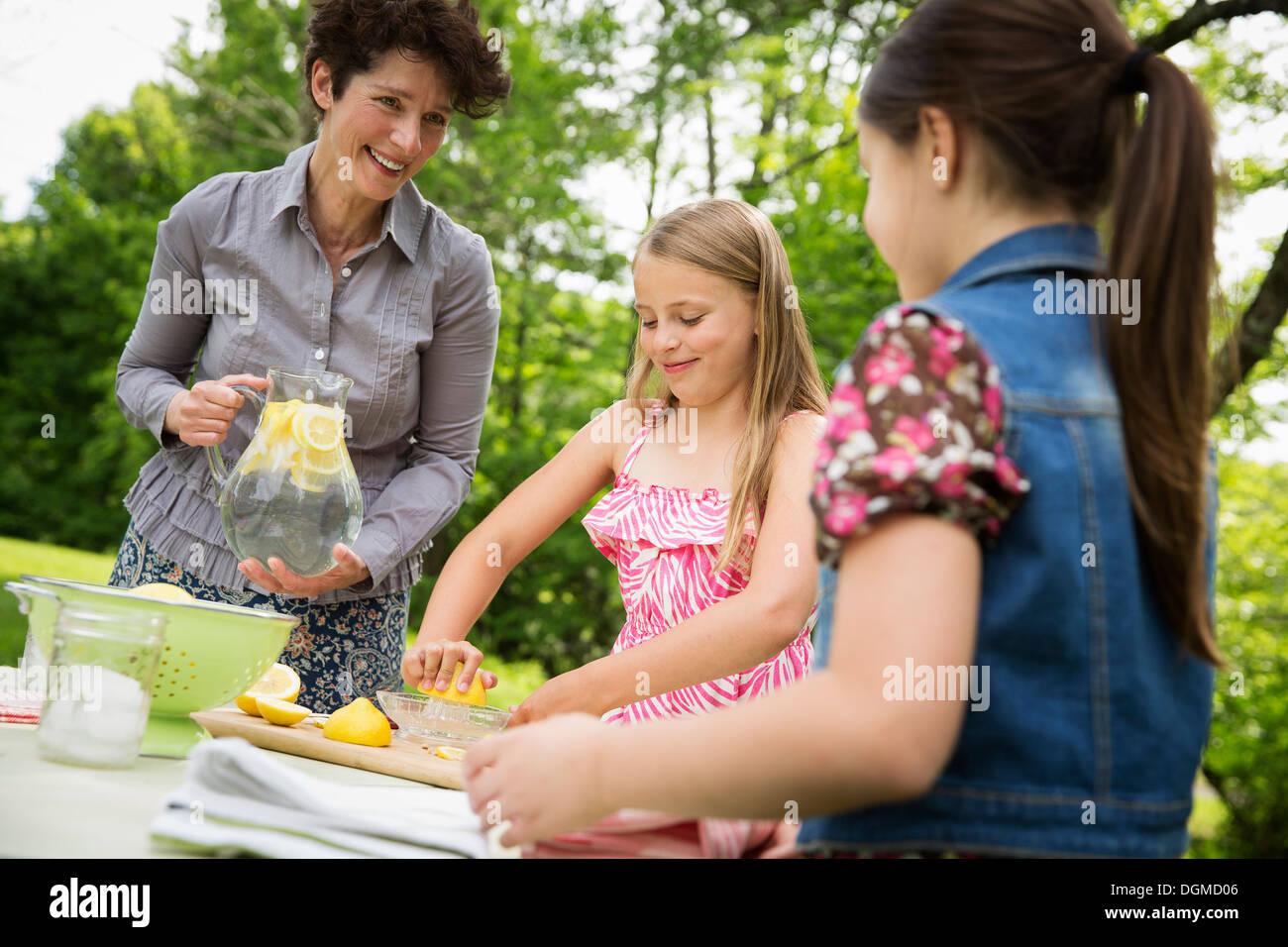 Un estate incontro di famiglia in una fattoria. Una donna e due bambini in piedi fuori da una tabella, che stabilisce la tabella. Facendo una limonata. Immagini Stock
