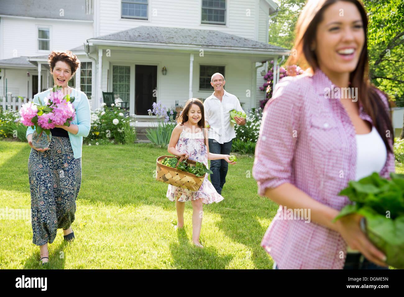 Festa di famiglia. I genitori e i bambini che trasportano fiori freschi raccolti di frutta e verdura. Per preparare a parte. Immagini Stock