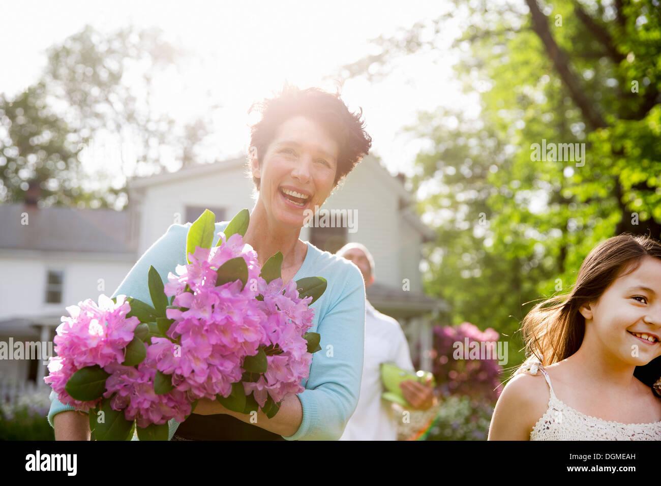 Festa di famiglia. Una donna che porta un grande mazzo di fiori di rododendro, sorridente largamente. Immagini Stock