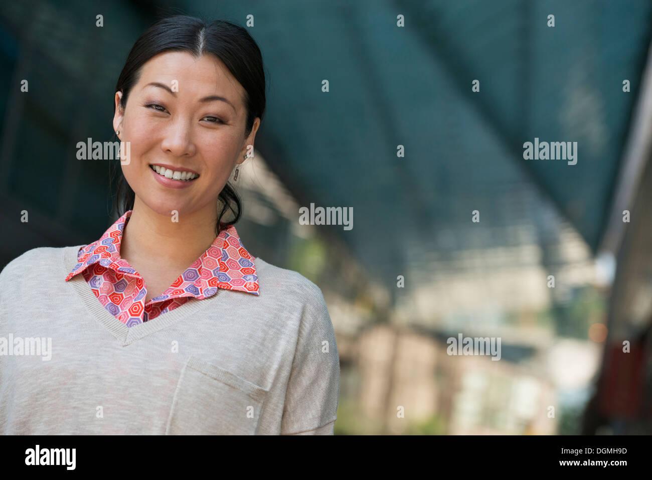 La gente di affari in movimento. Una donna in maglia rosa e maglione beige. Immagini Stock