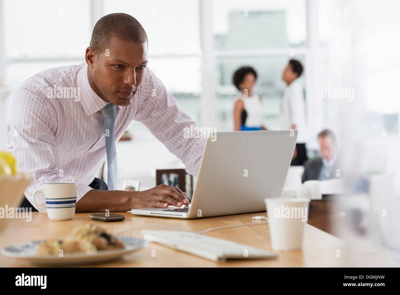 Ufficio. Un giovane uomo che utilizza un computer portatile su una scrivania. Immagini Stock
