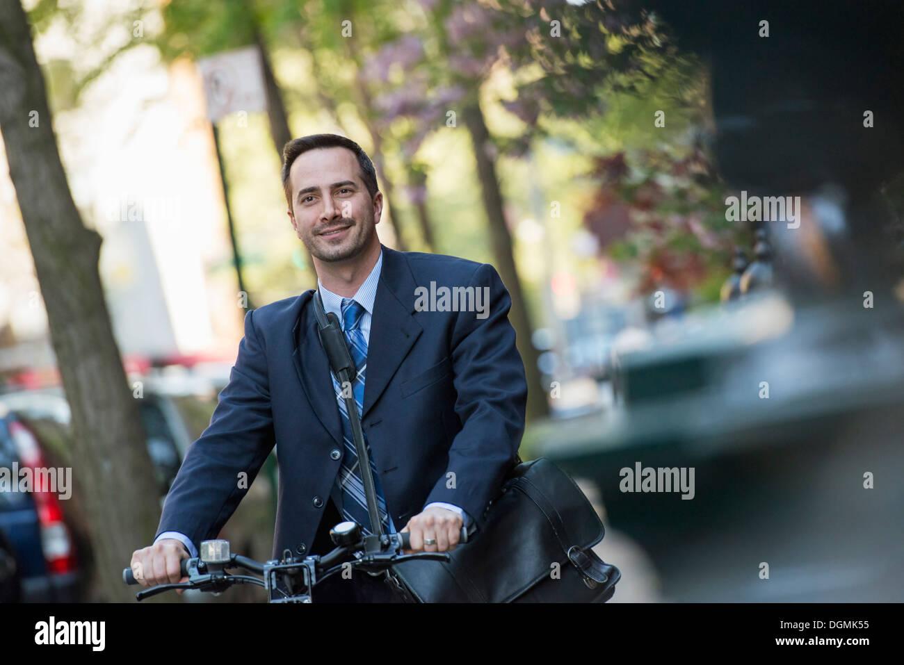 Un uomo in un business suit, all'aperto in un parco. Seduto su di una bicicletta. Foto Stock
