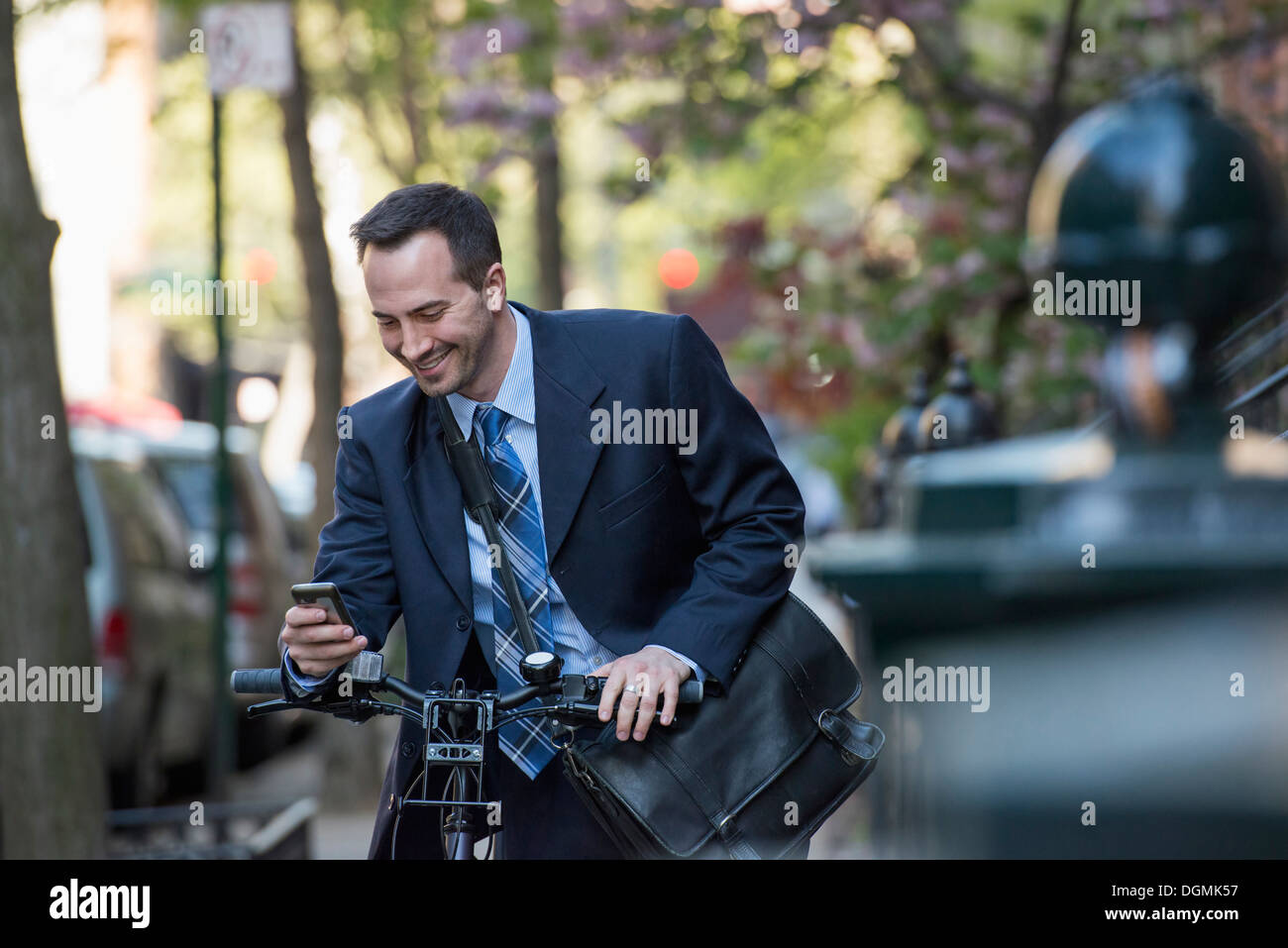 Un uomo in un business suit, all'aperto in un parco. Seduto su di una bicicletta. Foto Stock