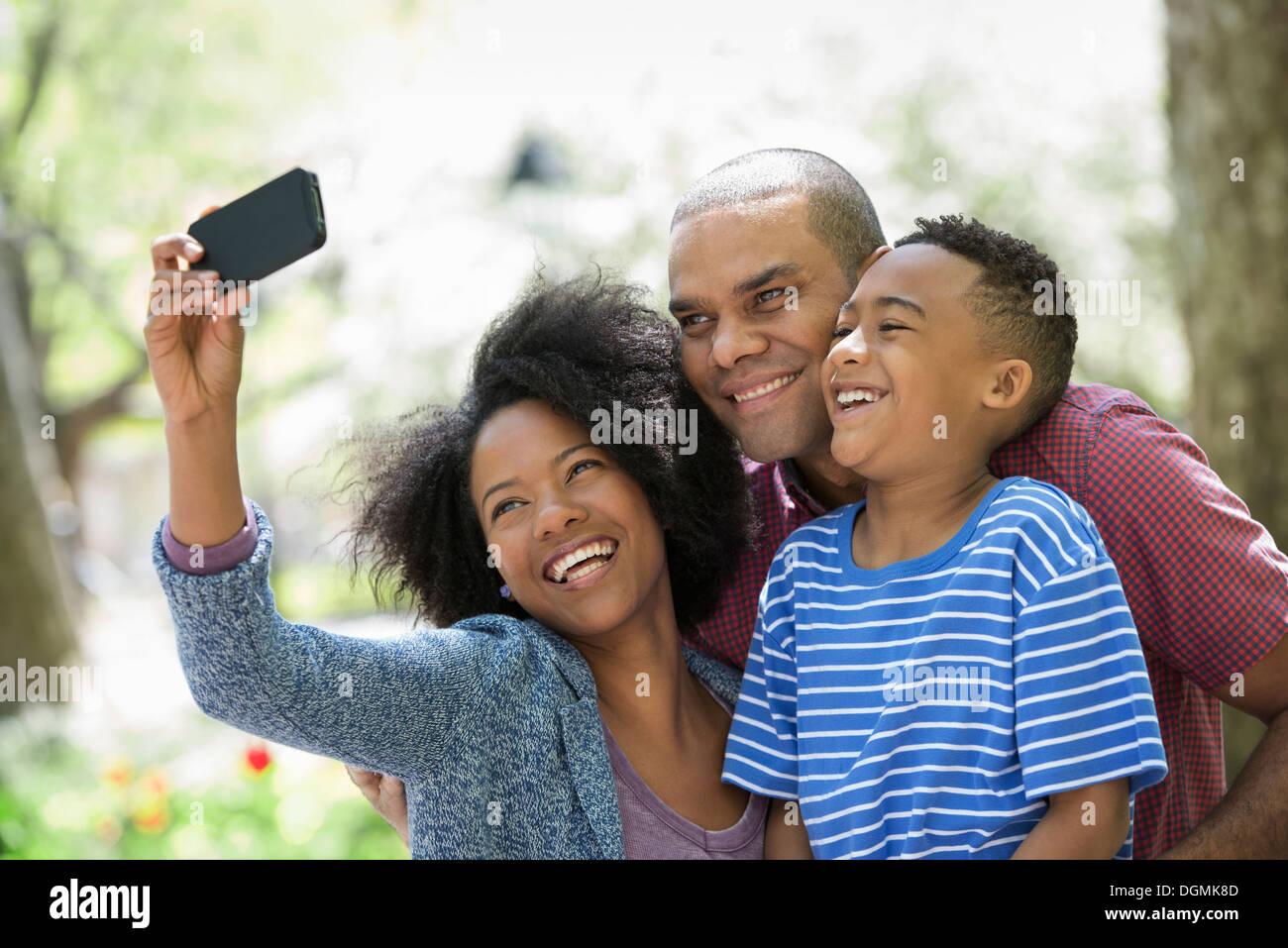 Due adulti e un ragazzino scattare fotografie con un telefono intelligente. Immagini Stock