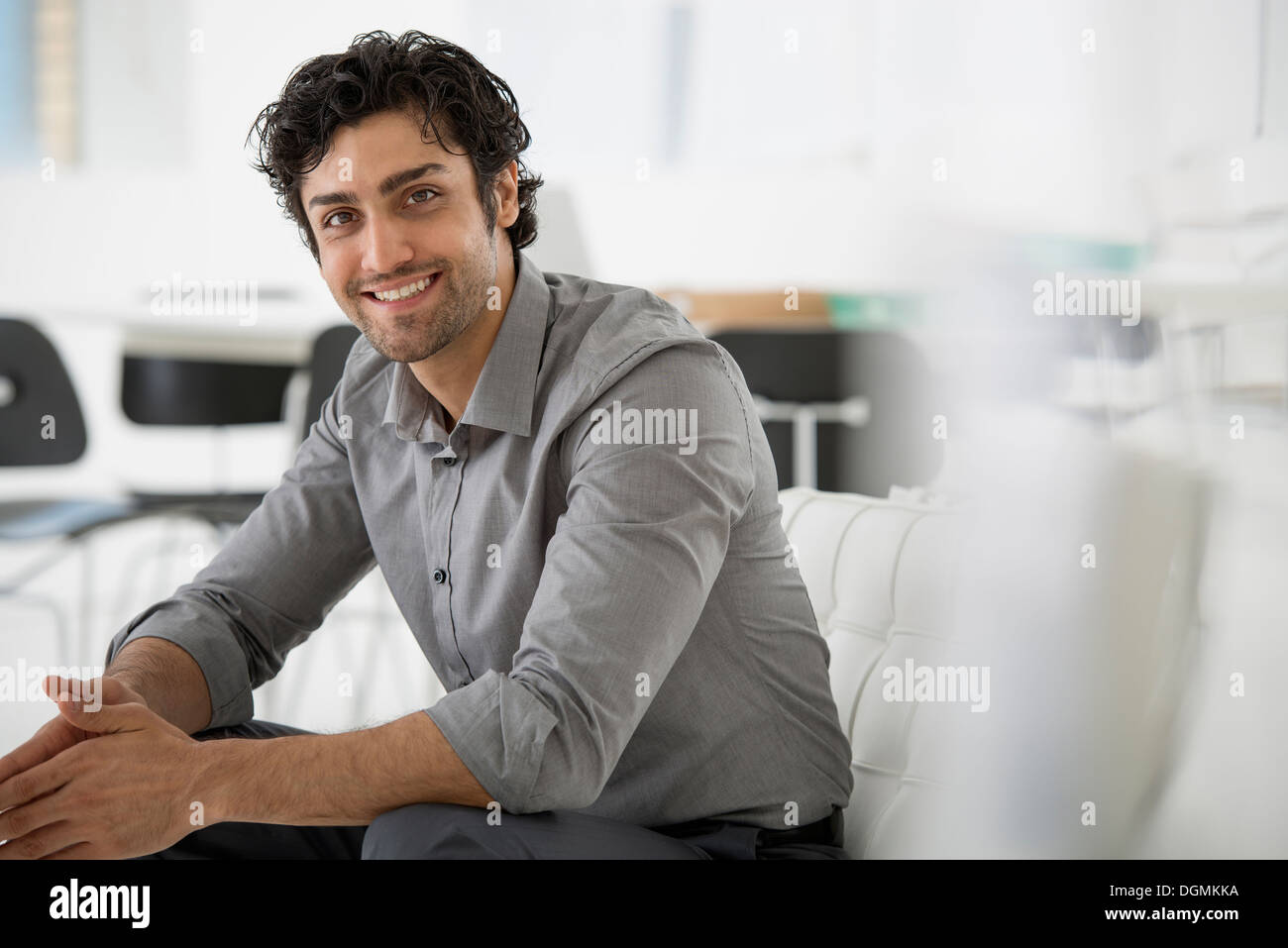 Business. Un uomo seduto con le mani giunte in una posa rilassata. Sorridente e inclinato in avanti. Immagini Stock