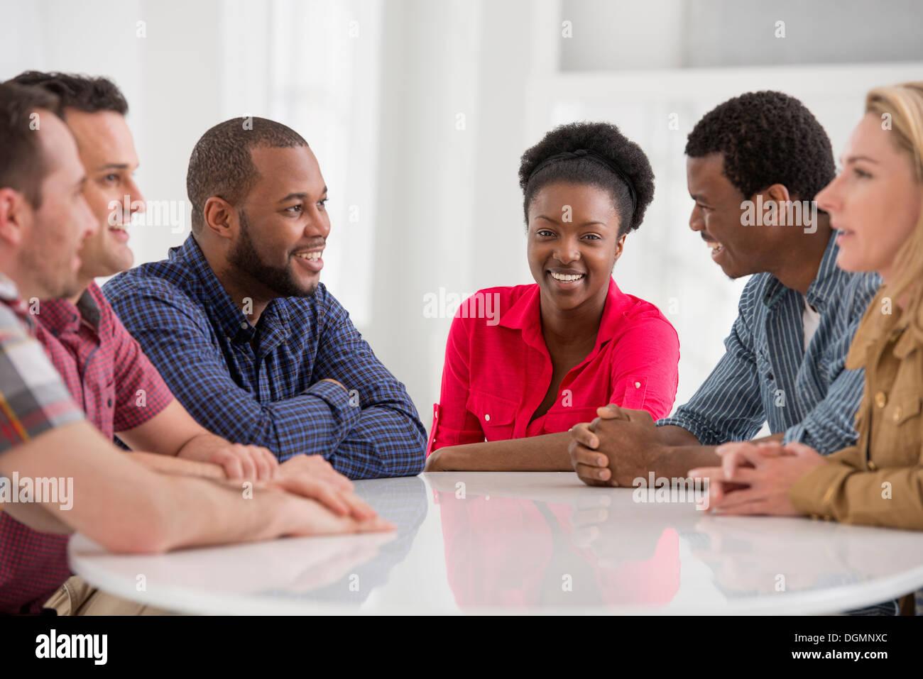 Ufficio. Un gruppo di quattro persone, due uomini e due donne seduti a parlare. Foto Stock