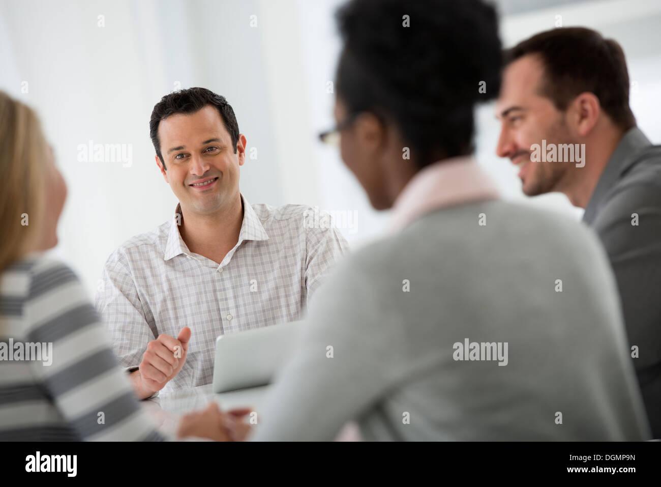 Ufficio interno. Un gruppo di quattro persone, due uomini e due donne, seduti attorno ad un tavolo. Riunione di Foto Stock