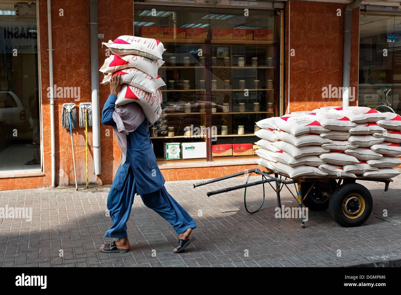 Lavoratore trasportare sacchi di lenticchie sulla sua spalla, Deira, Vecchio Souk di Dubai, Emirati Arabi Uniti, Medio Oriente Immagini Stock