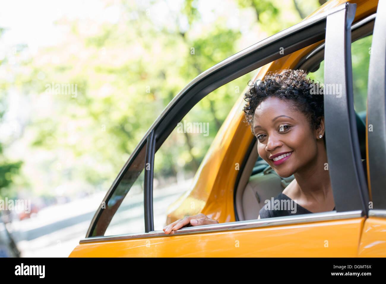 Una donna di uscire dalla parte posteriore del sedile passeggero di un taxi giallo. Immagini Stock