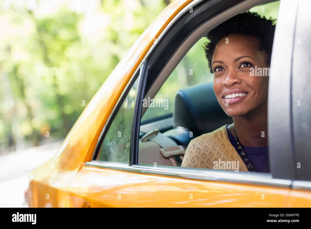 Una donna seduta nella parte posteriore del sedile passeggero di un taxi giallo. Immagini Stock