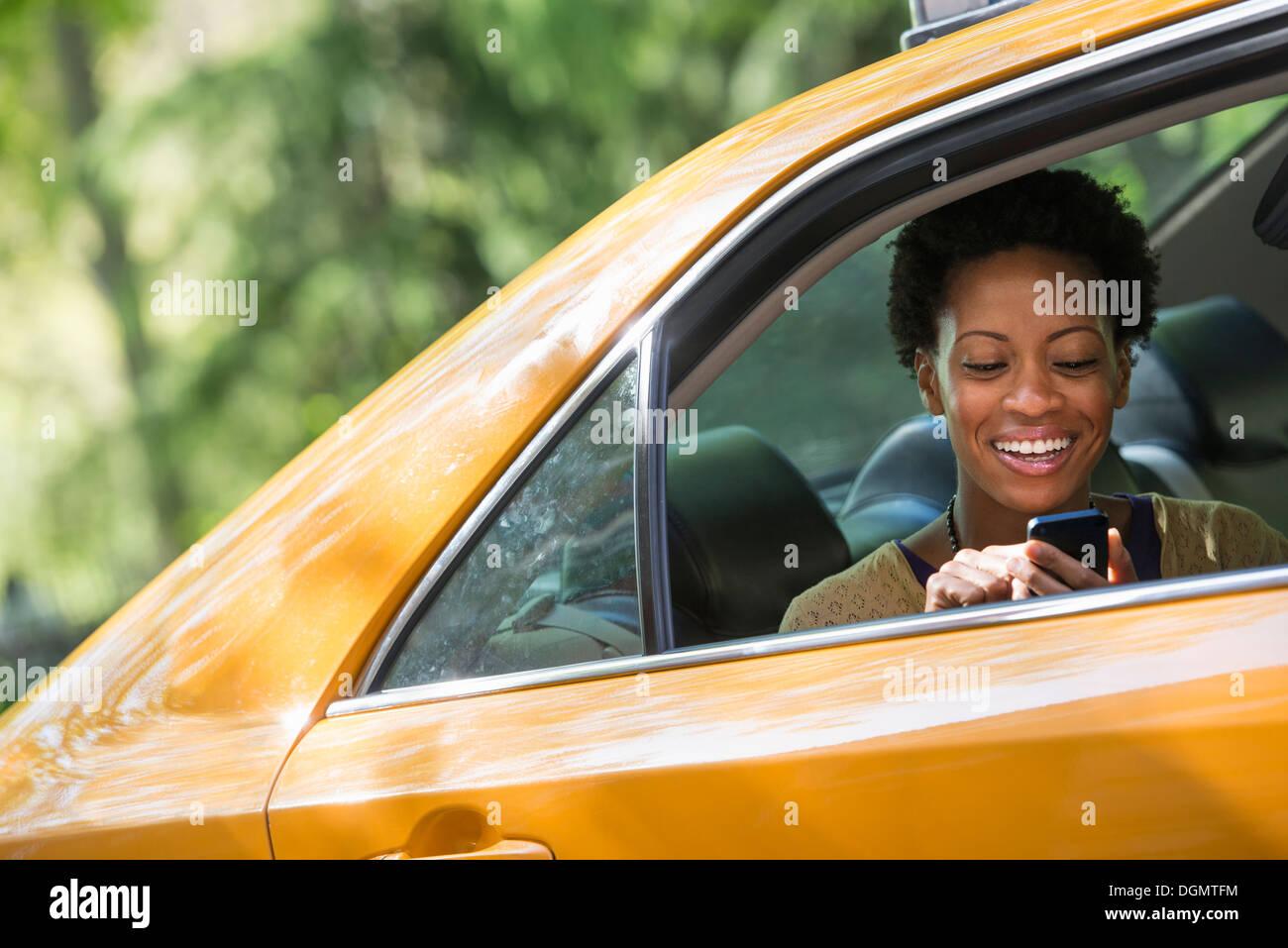 Una donna seduta nella parte posteriore del sedile passeggero di un taxi giallo, controllando il suo telefono. Immagini Stock