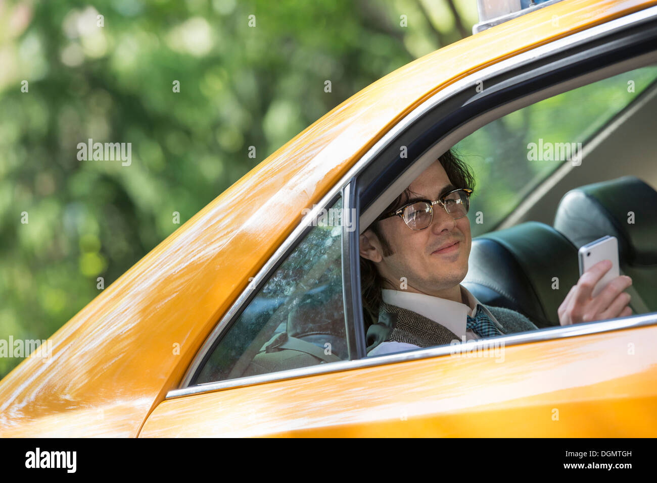 La vita della città. Le persone in movimento. Un giovane uomo nel sedile posteriore di un taxi. Immagini Stock