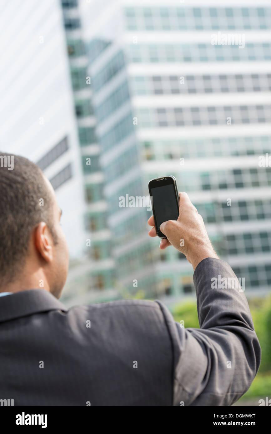 Città. Un uomo in un business suit tenendo la sua smart phone per la lunghezza del braccio. Immagini Stock