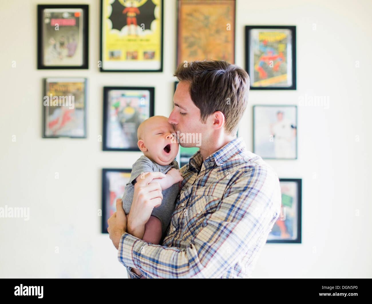 Padre kissing baby figlio (2-5 mesi) Immagini Stock