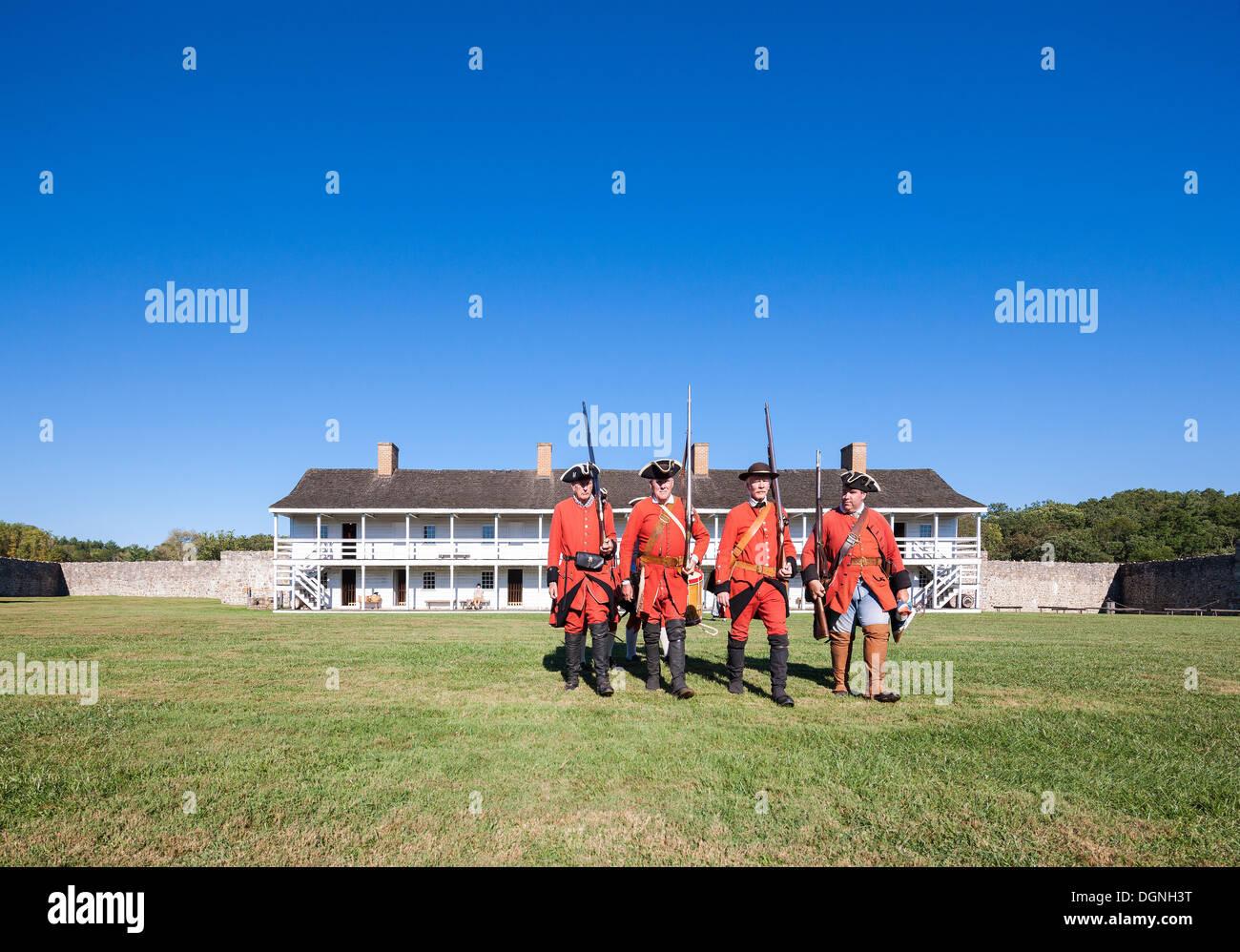 Storica del XVIII secolo nella vita quotidiana a Fort Frederick Maryland. Volontari marzo con periodo di uniformi e moschetti. Oriente caserma. Immagini Stock