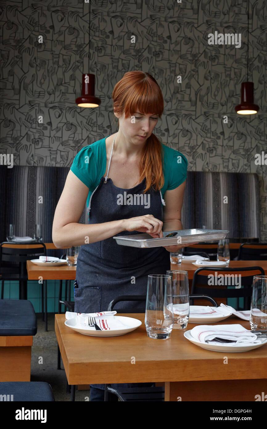 Metà donna adulta la preparazione di tabella nel ristorante Immagini Stock