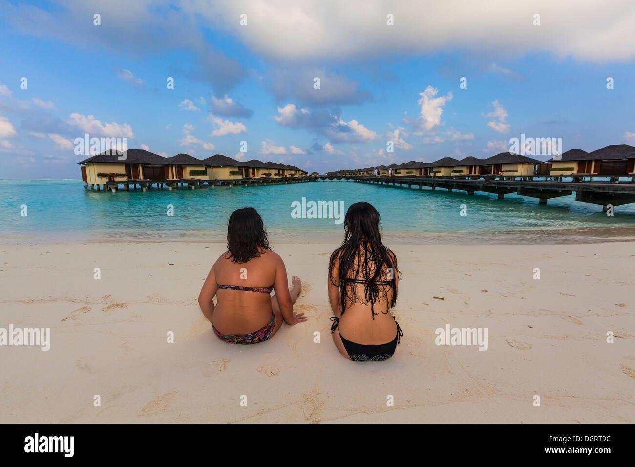 Due ragazze, circa 15 e 19 anni seduto sulla spiaggia, laguna, Paradise Island all'indietro, Lankanfinolhu, North Male Atoll Immagini Stock