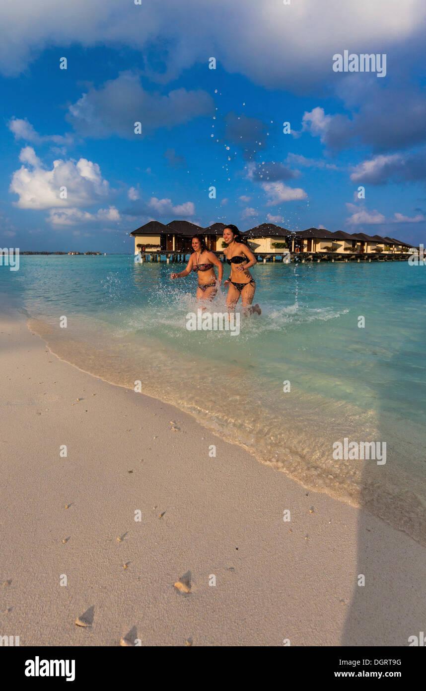 Due ragazze felici, circa 15 e 19 anni, in esecuzione su una spiaggia, laguna, Paradise Island all'indietro, Lankanfinolhu Immagini Stock