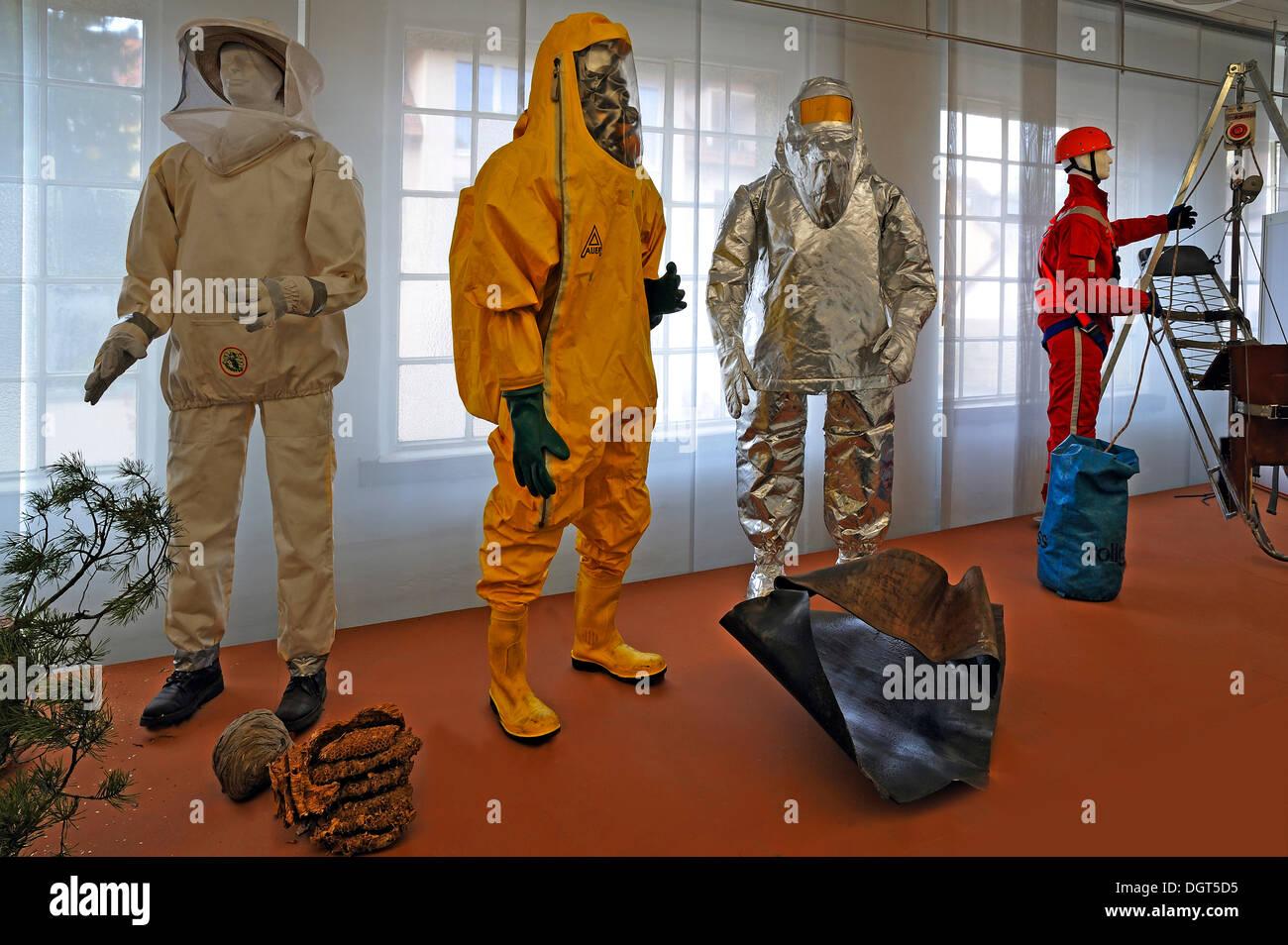 Diversi indumenti di protezione per vigili del fuoco, un insetto abbigliamento protettivo, una tuta di protezione chimica con una maschera per la respirazione, una Immagini Stock