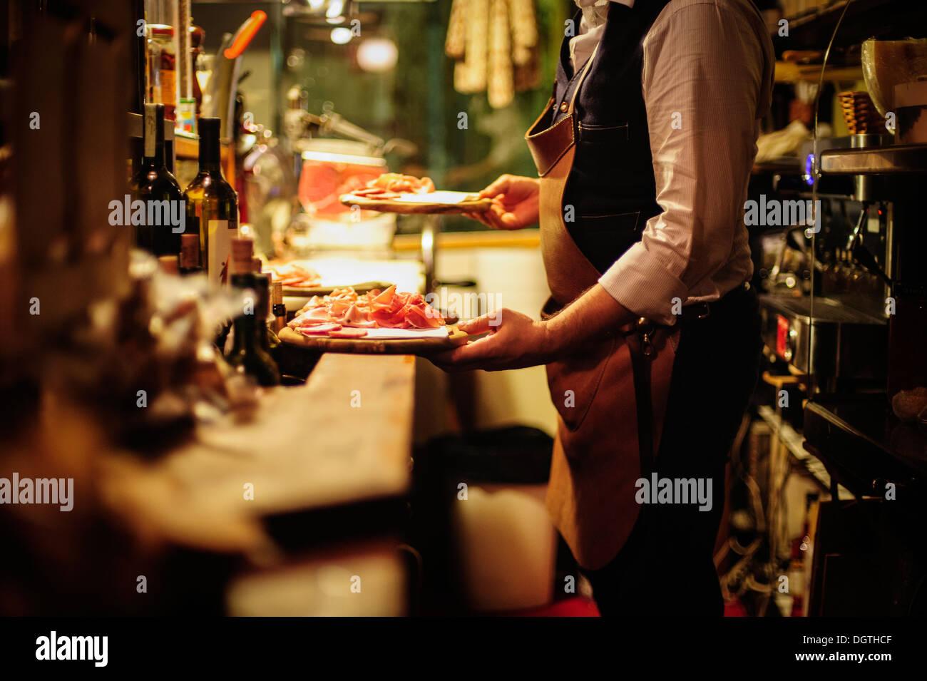 Un server che trasportano un plater di carni secche a La Mascareta ristorante, Venezia, Italia. Immagini Stock