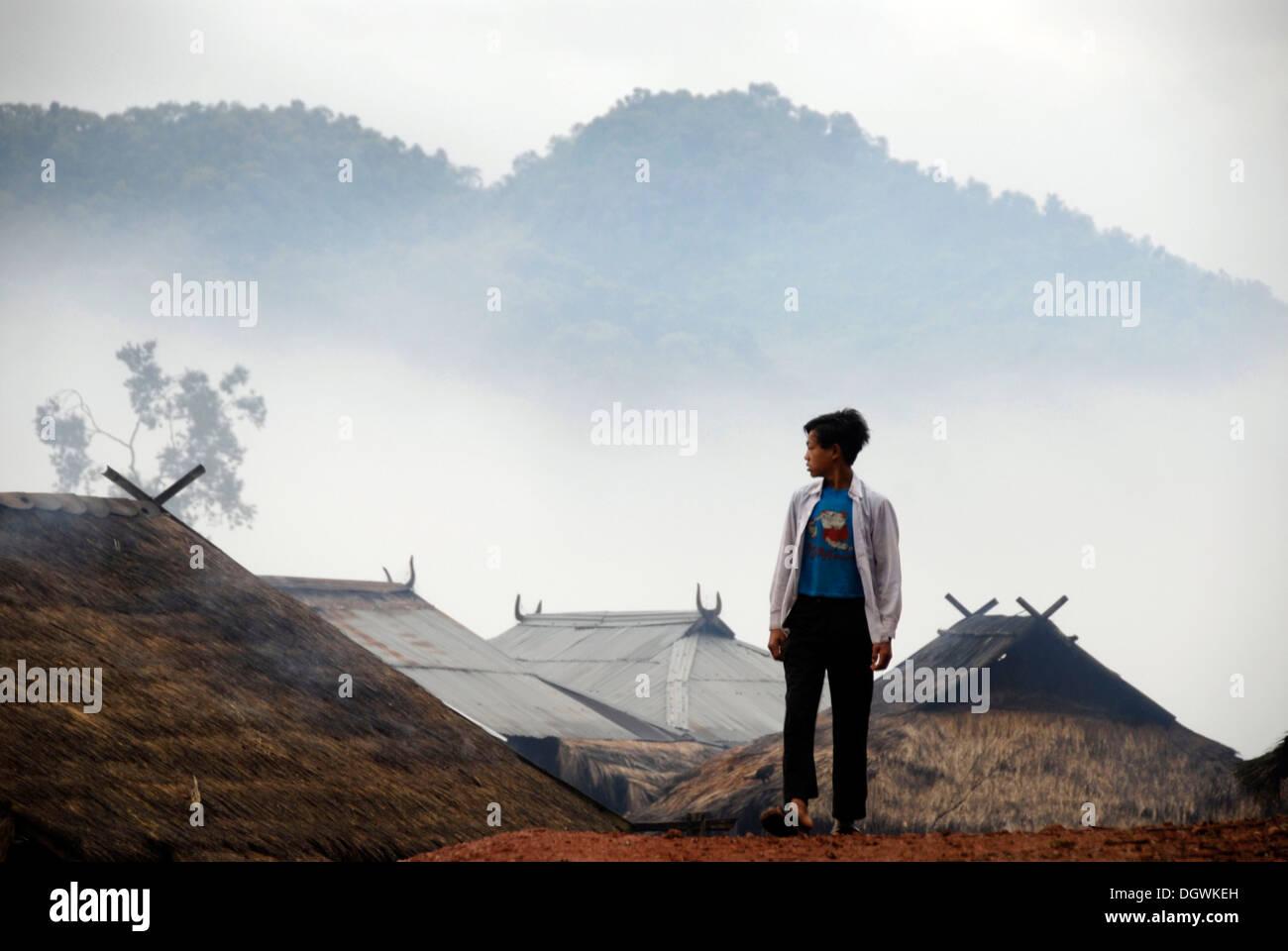 Ragazzo nella parte anteriore del case del Phixor Akha gruppo etnico, divieto di villaggio Mososane, i tetti di paglia, nebbia e montagne Immagini Stock