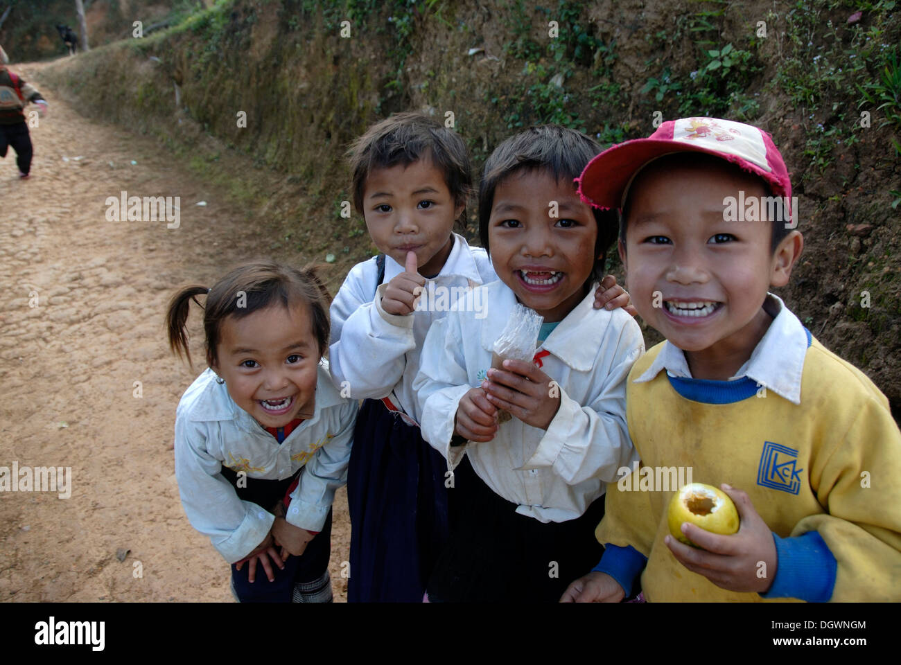 I bambini, la povertà, la pista di grinning bambini divertirsi, villaggio di Ban Komaen, Phongsali distretto e provincia, Laos Immagini Stock