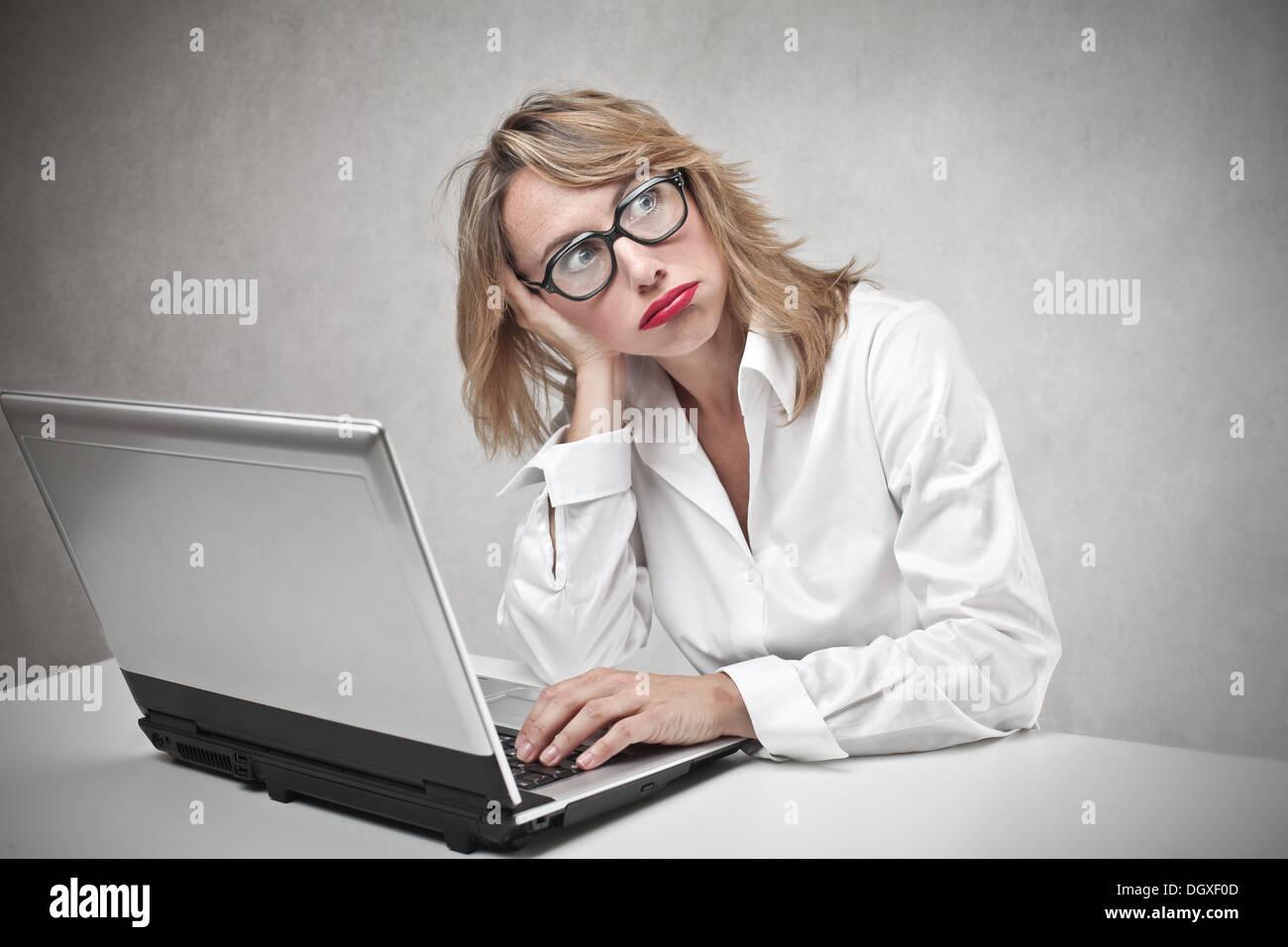 Annoiato donna bionda con gli occhiali usando un computer portatile Immagini Stock