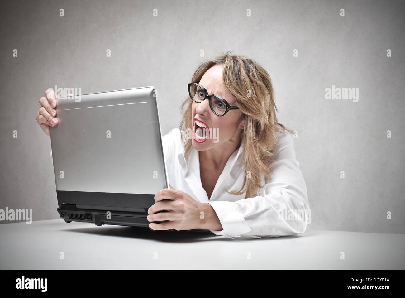 Donna bionda con gli occhiali urlando contro un computer portatile Foto Stock