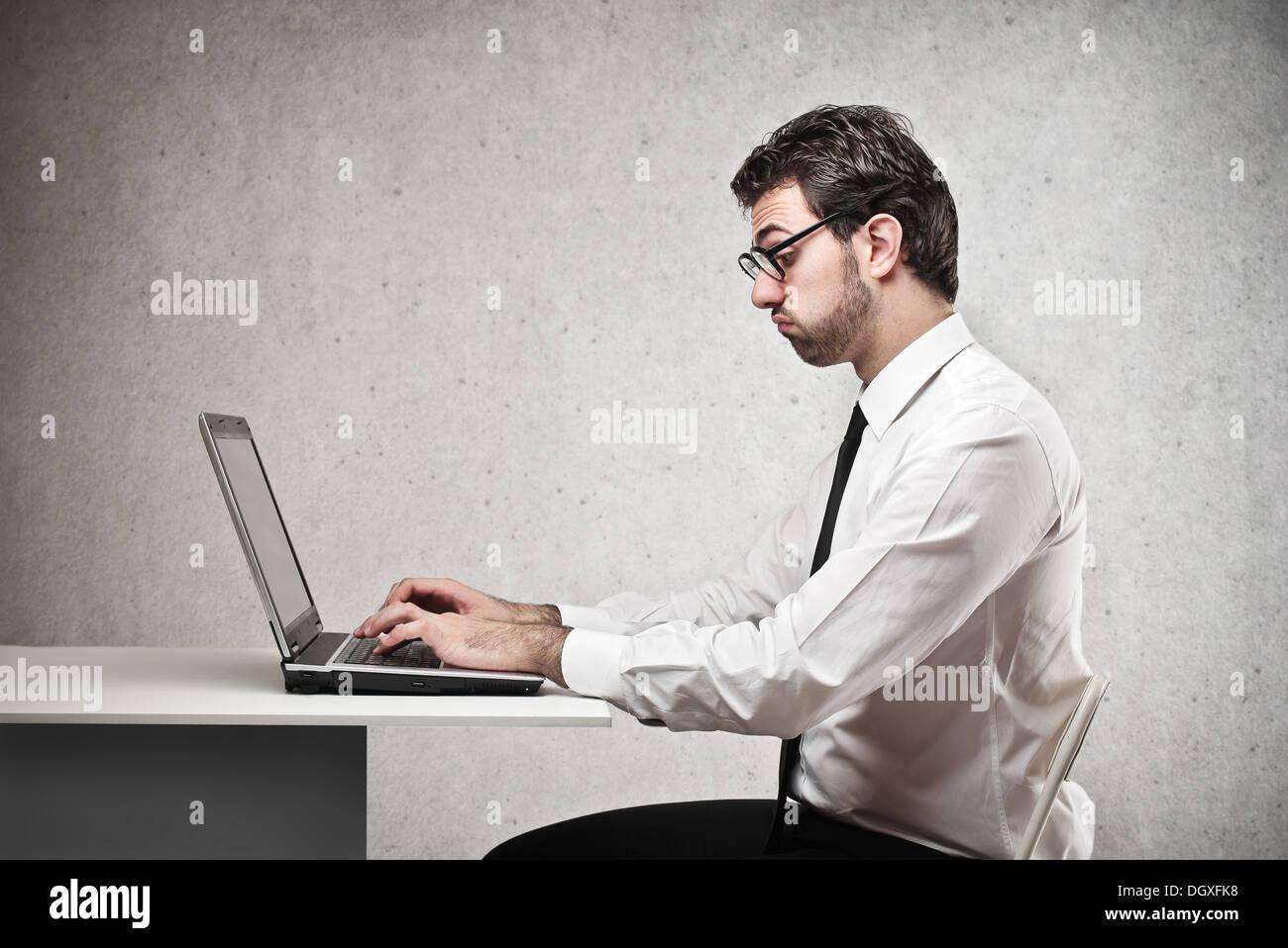 Lavoratore di ufficio utilizzando un computer portatile Immagini Stock