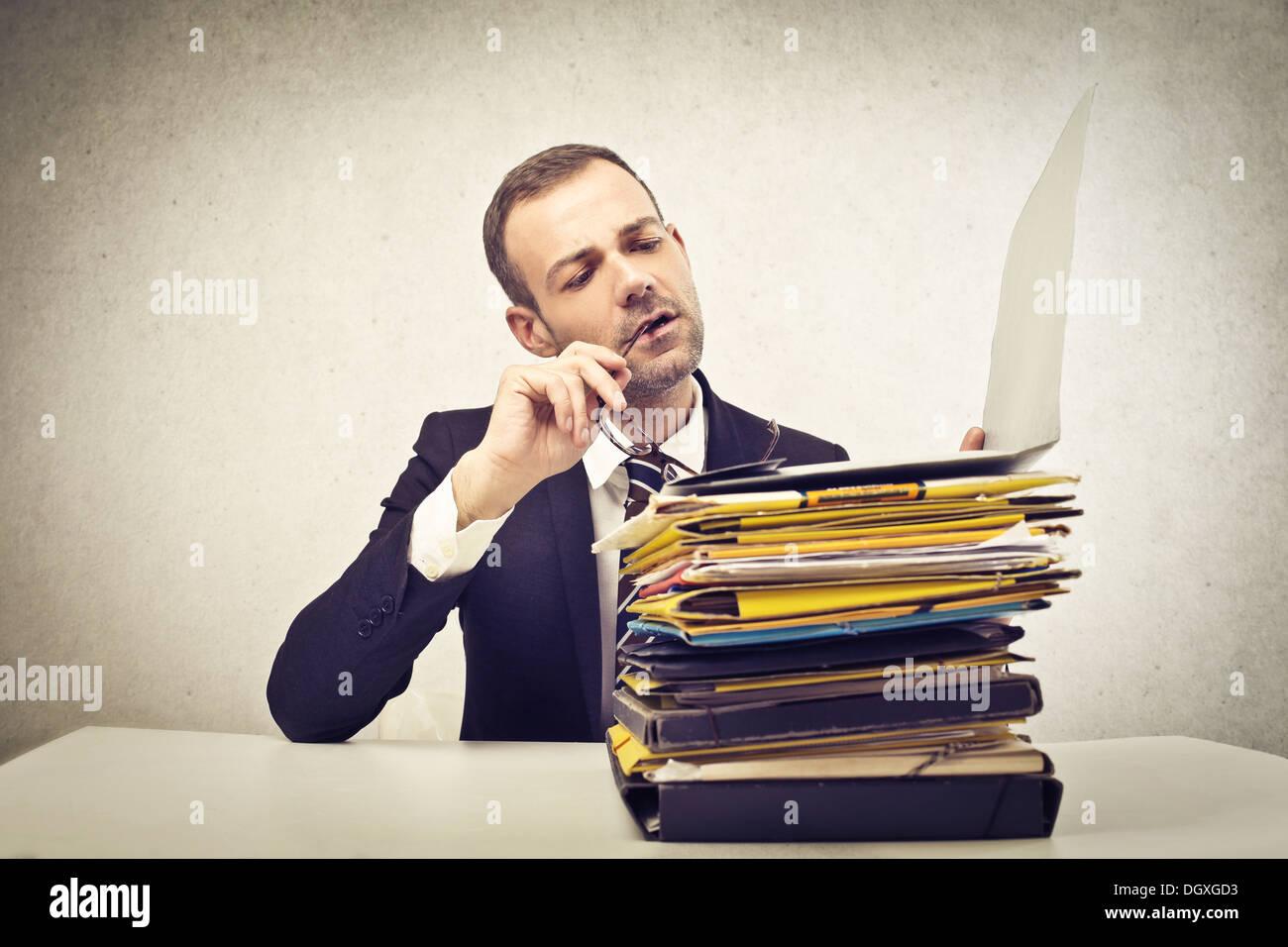 Giovane imprenditore la lettura di una pila di carte Immagini Stock