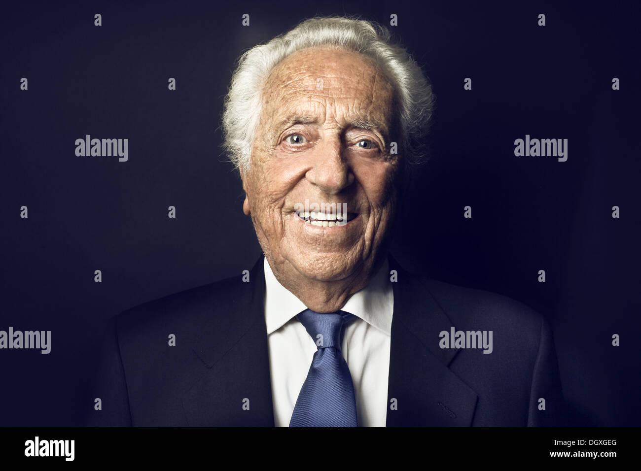 Sorridente vecchio uomo su sfondo nero Immagini Stock