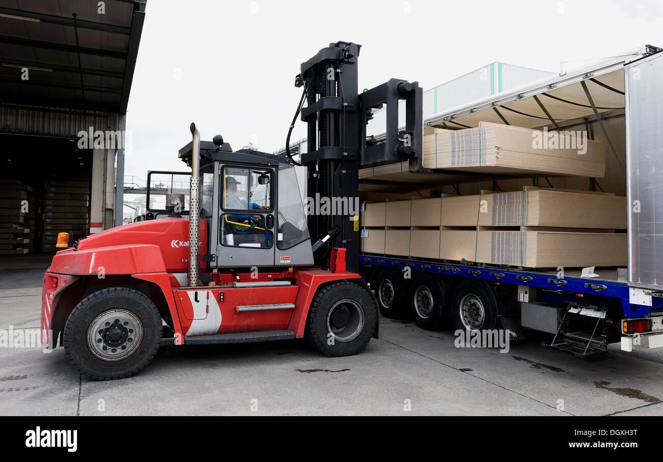 Forca di carico del sollevatore il finito di assi di particella su un camion, Pfleiderer AG fabbrica presso la sede Foto Stock