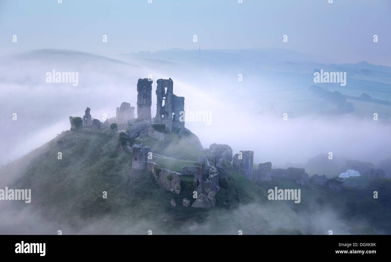 Corfe Castle Rising attraverso la mattina presto nebbie Immagini Stock