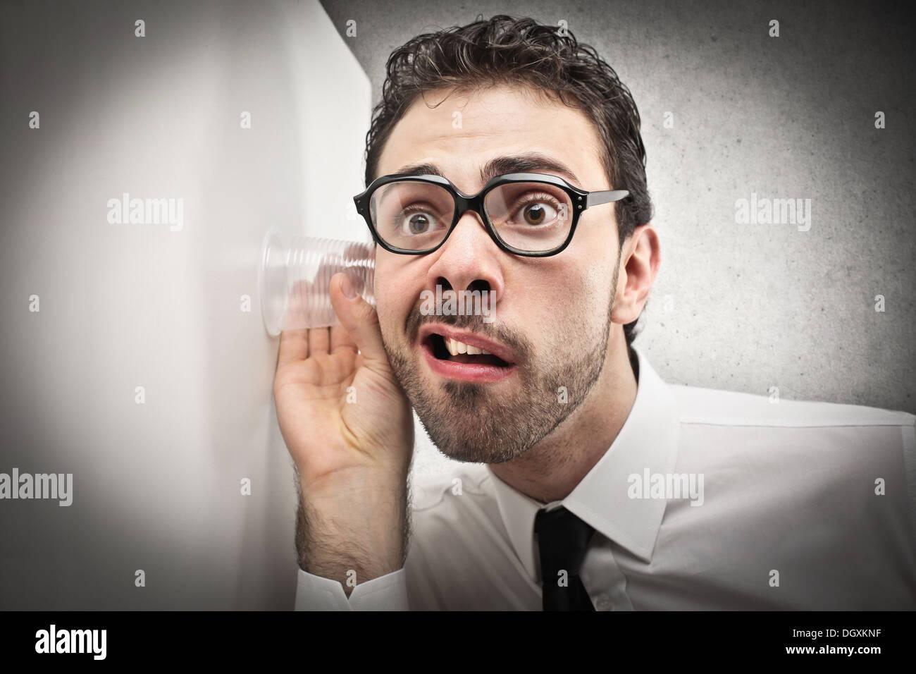 Lavoratore di ufficio con gli occhiali cercando di sentire attraverso una parete Immagini Stock