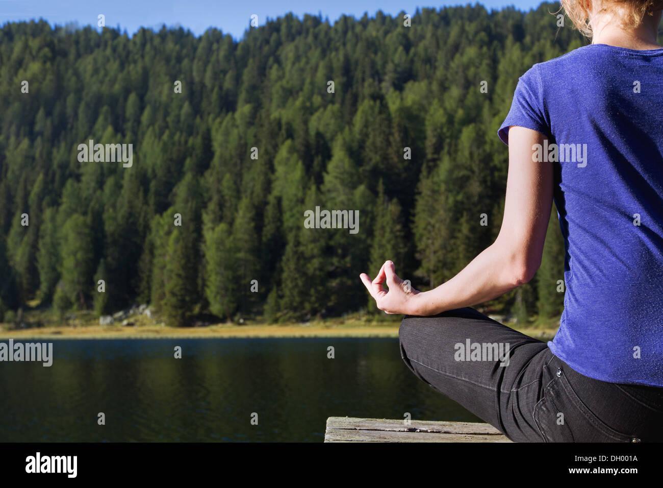 Lo yoga e la meditazione vicino lago di montagna Immagini Stock