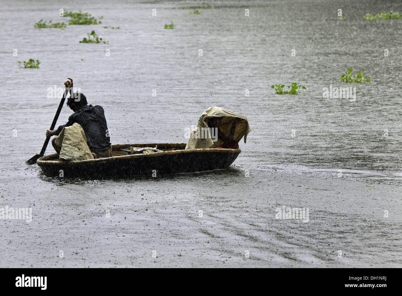 L'uomo Canottaggio Kayak rotondi punnamada in barca il lago di Alleppey Kerala India Immagini Stock