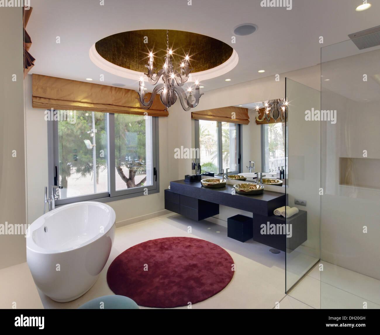Oval Freestanding Vasca Circolare E Tappeto Nel Bagno Moderno Con Luce Centrale Di Raccordo E Grandi Finestre Foto Stock Alamy