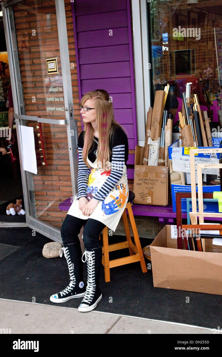 Arte giovane donna seduta al suo negozio di telaio indossare top ...