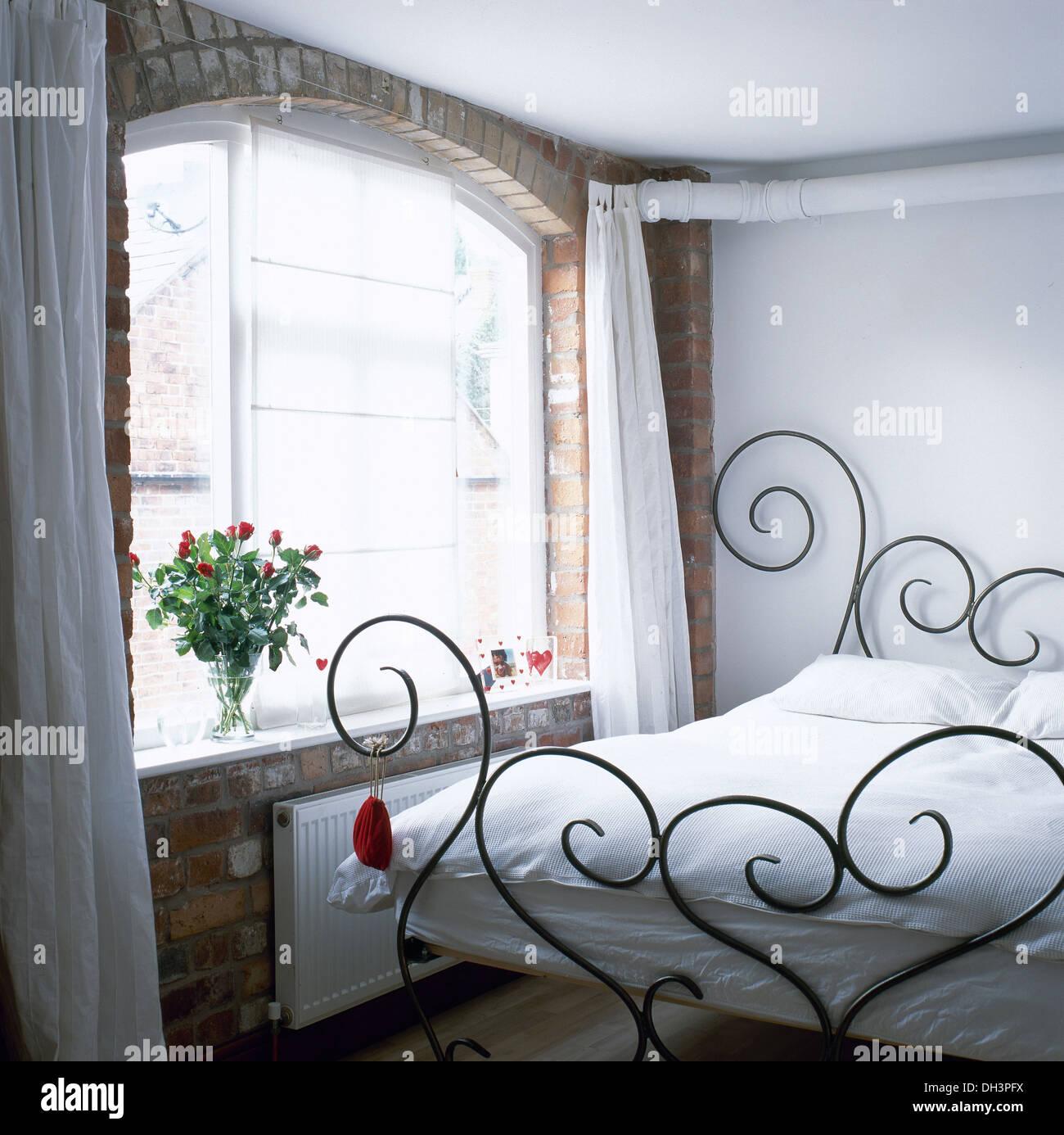 Decorativi in ferro battuto letto con lenzuola bianche in semplice ...