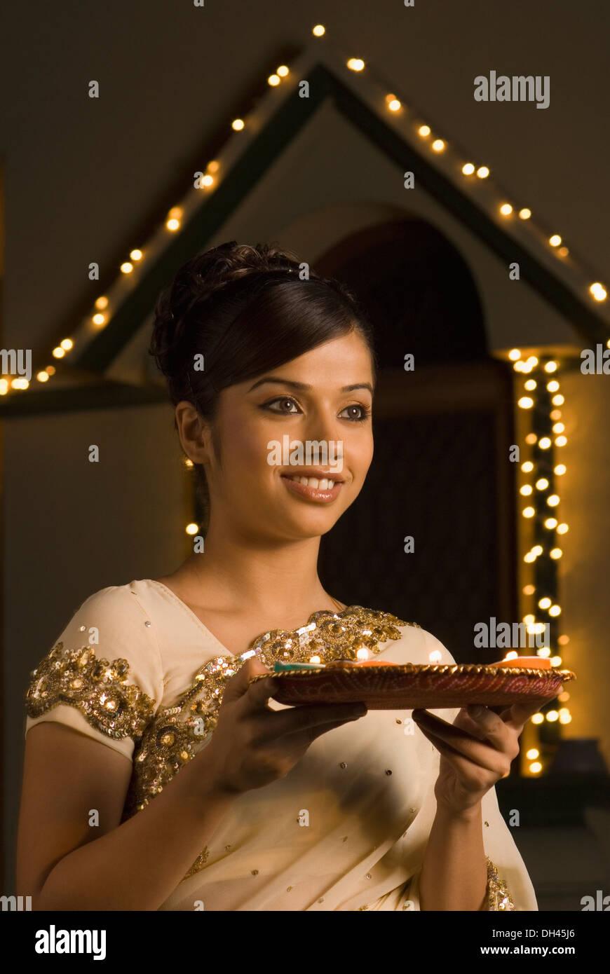 Donna che mantiene i religiosi che offrono e sorridente Foto Stock