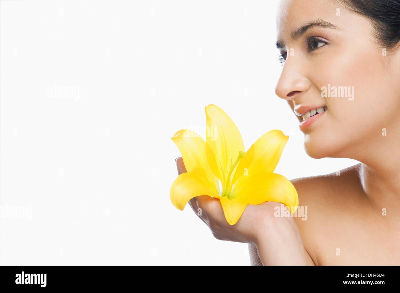 Donna che mantiene un fiore Foto Stock