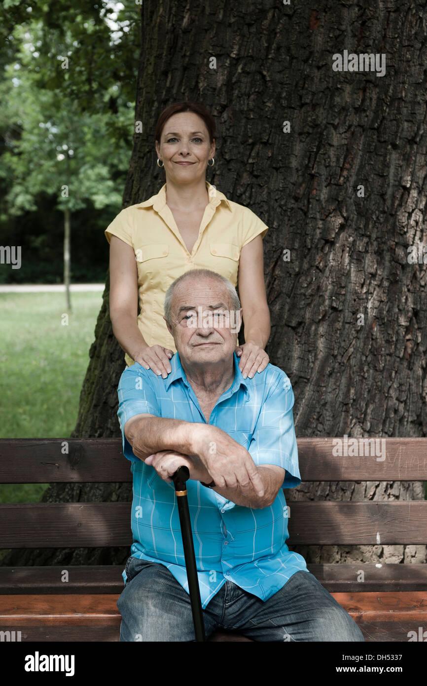 Donne Cercando dopo un anziano uomo seduto su una panchina nel parco Foto Stock