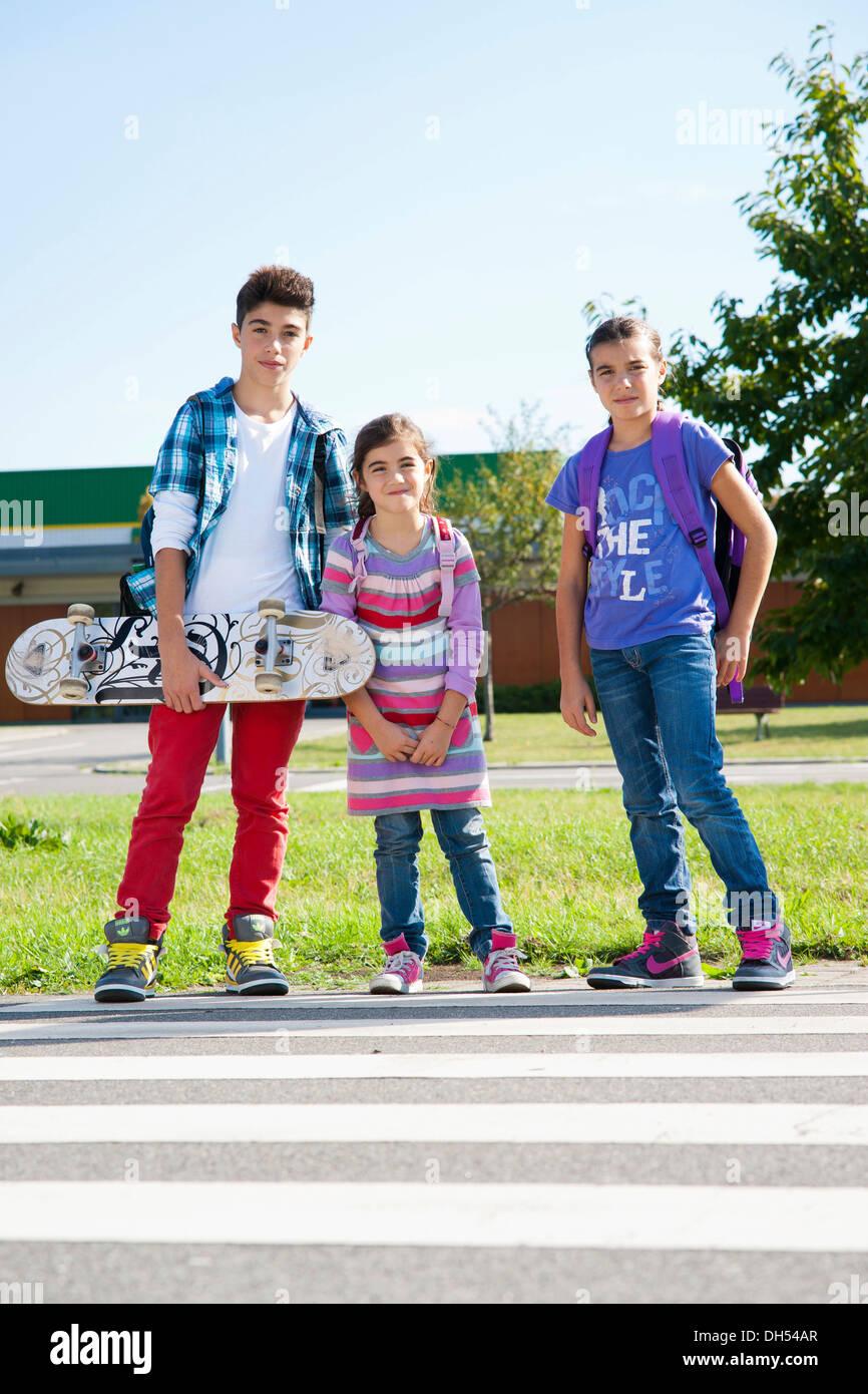 I bambini con uno skateboard e portante scuola di sacchi sulla strada per la scuola Immagini Stock