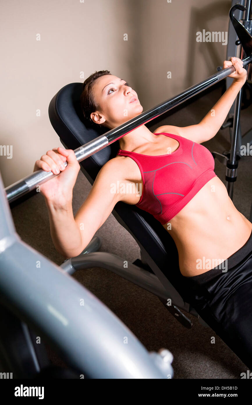 Giovane donna il sollevamento pesi in una palestra Immagini Stock