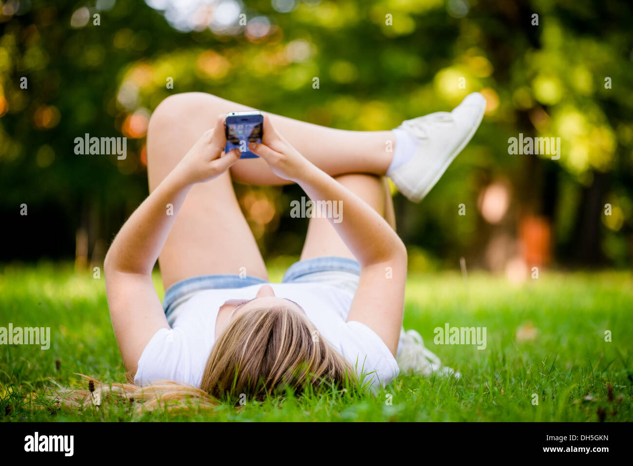Giovane donna sdraiata su erba e lavorando con lo smartphone Immagini Stock