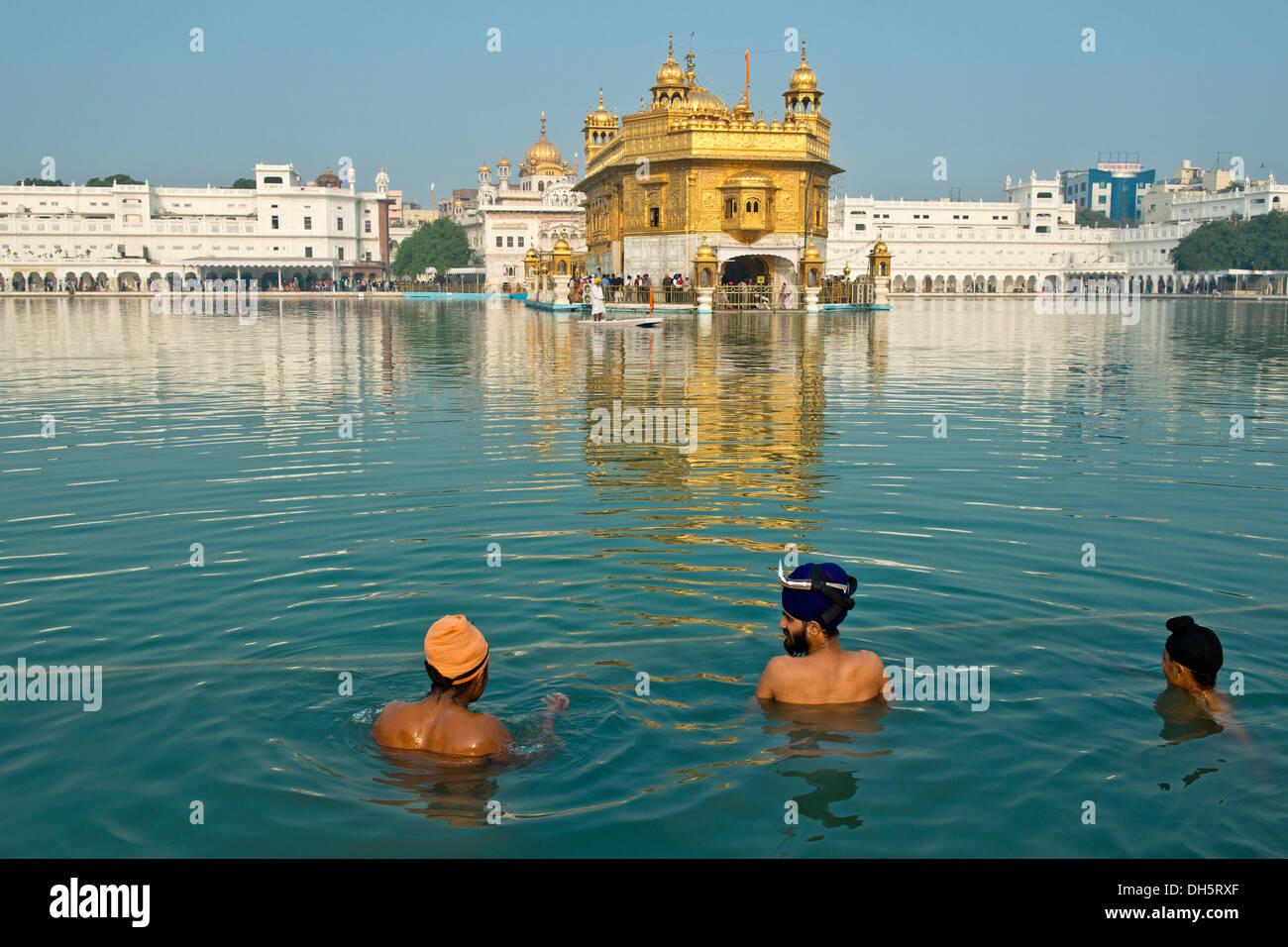 Tempio d'oro, Hari Mandir, il principale santuario della religione sikh, tre pellegrini indossa turbanti di prendere un bagno rituale nel lago santo di Foto Stock