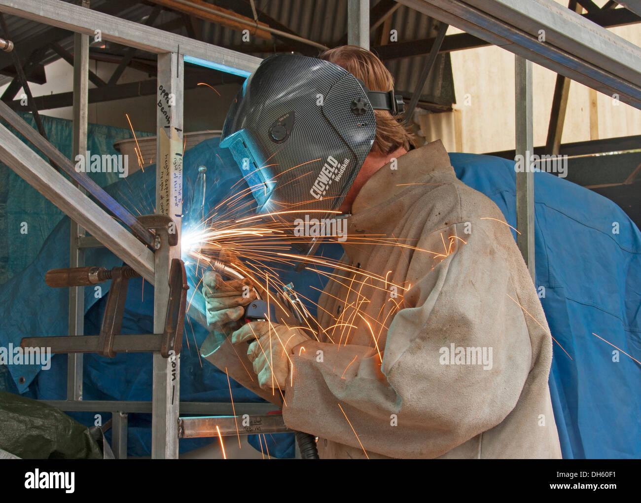 Saldatore di indossare abbigliamento protettivo e casco per saldatura tubo di acciaio quadro con scintille battenti dalla bacchetta di saldatura Immagini Stock