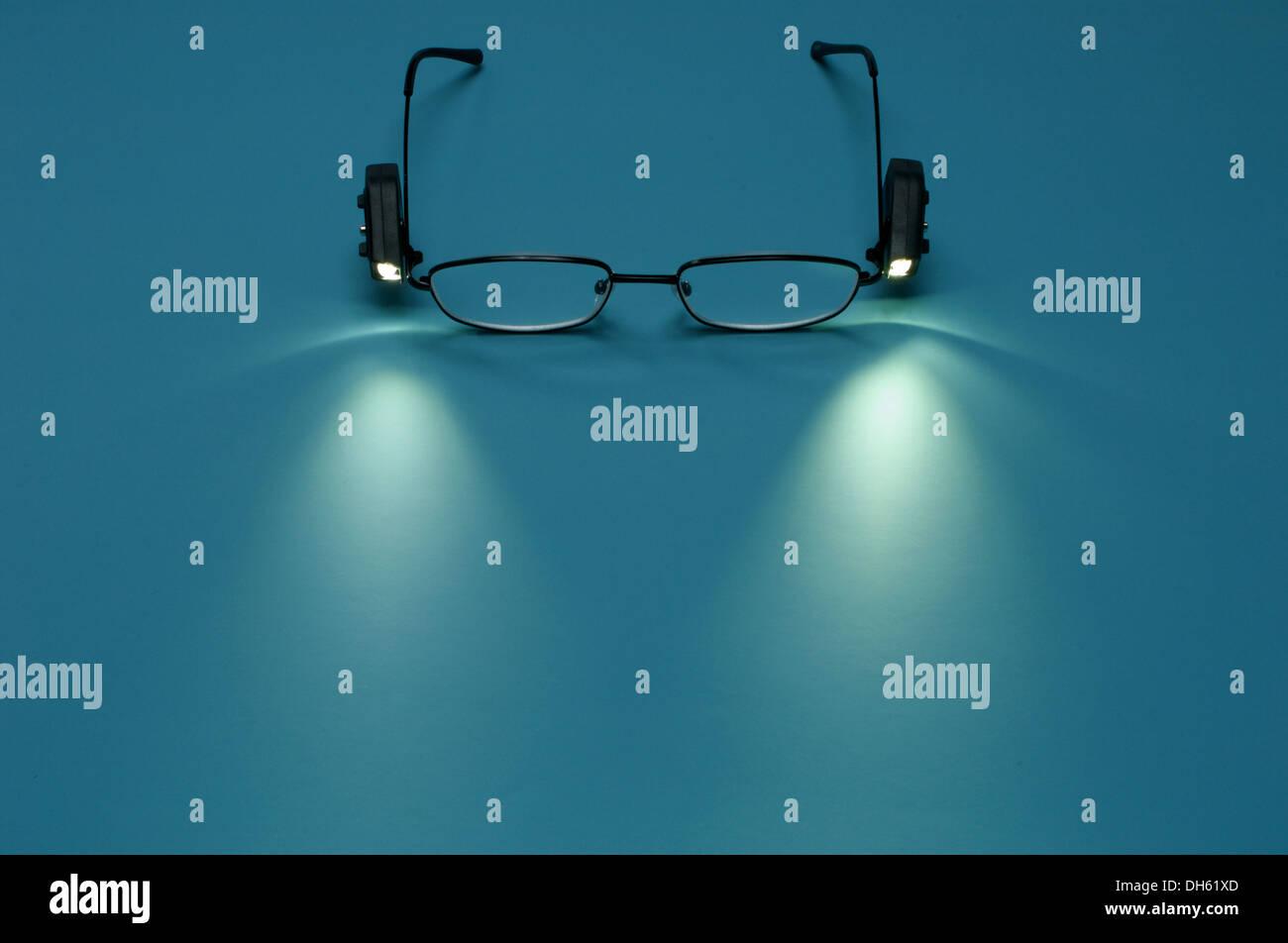 Un paio di occhiali da lettura con piccole luci allegata Immagini Stock